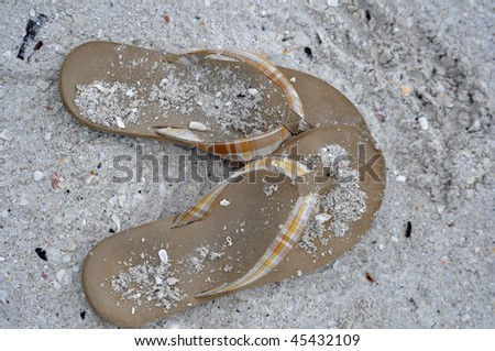 a pair of flip-flops sit on a sandy and shelly beach - stock photo