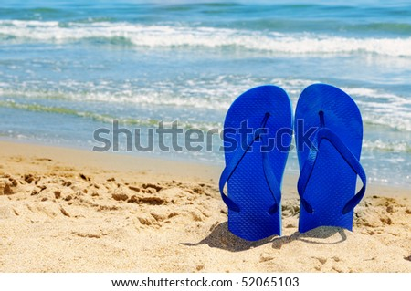 a pair of flip-flops stuck on the sand of a beach - stock photo