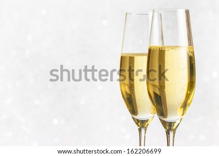 a pair of flutes of golden champagne on silver bokeh background and space for text - stock photo
