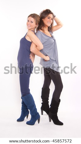 A pair of girls back to back smiling to the camera - stock photo