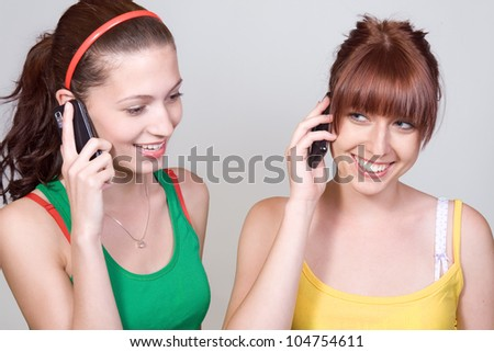 A pair of girls on the phone together