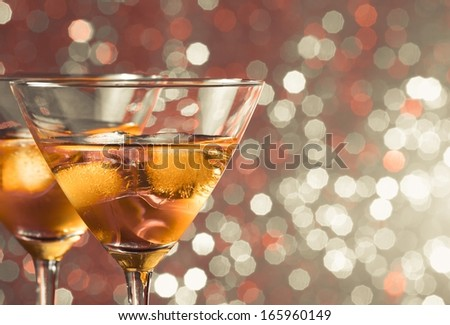 a pair of glasses of fresh cocktail with ice on  light bokeh background with space for text - stock photo