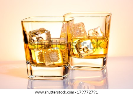 a pair of glasses of whiskey with ice on white bar table