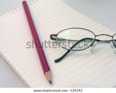 A pair of glasses on a blank note pad with a pencil.