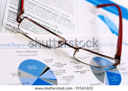 A pair of glasses on top of a financial report. - stock photo