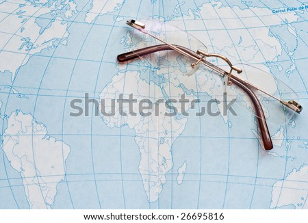 A pair of glasses over a geography atlas