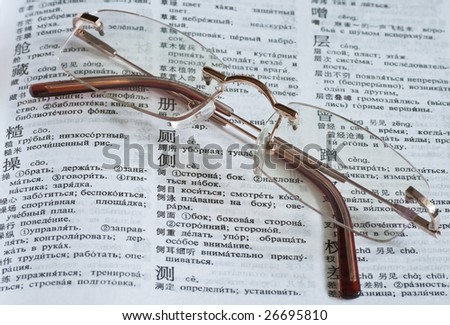 A pair of glasses over a Russian-Chinese dictionary