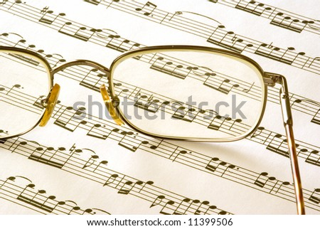 A pair of glasses sitting on sheet music