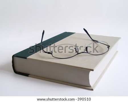 A pair of glasses that place on a closed book after finish reading - stock photo