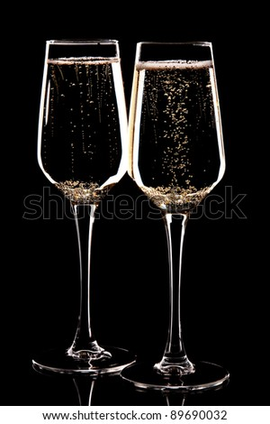 a pair of glasses with champagne on a black background
