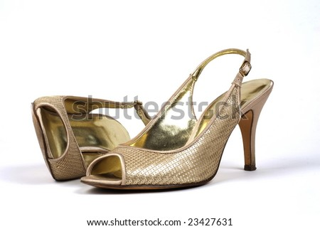 A pair of gold women's high-heel shoes against white background, one shoe standing, one shoe lying - stock photo
