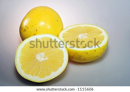 a pair of grapefruit, one sliced to expose the white fleshy interior