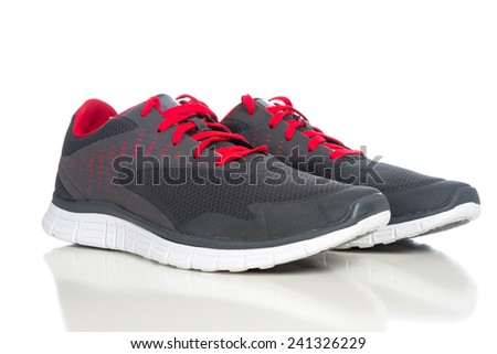 A pair of gray running shoes with red shoelaces on a white backg - stock photo