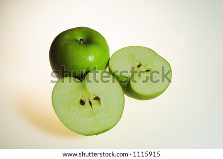 a pair of green apples with one left whole and the other sliced in half to show seeds and meat. - stock photo
