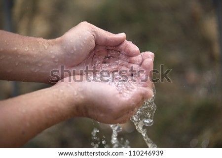 A pair of hands are cupped as they hold clear, trickling water. - stock photo