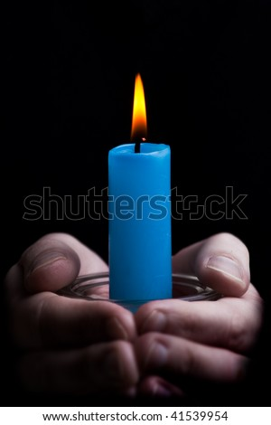 A pair of hands cupping a candle in symbolic gesture