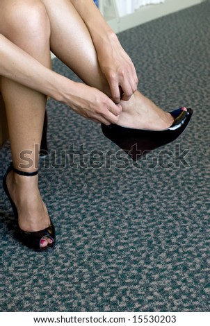 A pair of hands fix the strap of a shiny patent leather pump at the end of a pair of woman's legs. - stock photo