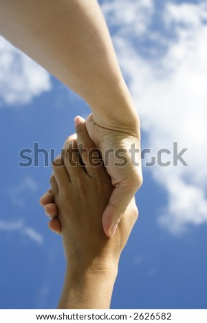 A pair of hands holding or shaking each other against a blue sky. Concept: Agreeement reached or helping hand. - stock photo