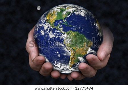 A pair of hands holding the Earth with the moon in the background. Blue Marble picture courtesy of NASA, see http://visibleearth.nasa.gov/useterms.php for terms of use - stock photo