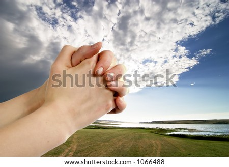 A pair of hands in a praying position set against a beautiful prairie lake landscape - stock photo