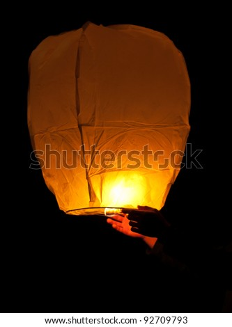 A pair of hands launching a Chinese Lantern