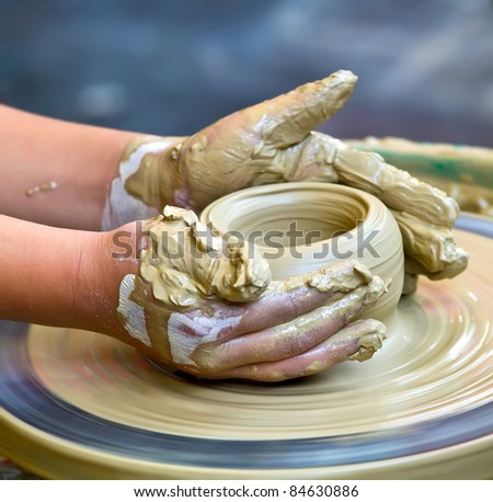 A pair of hands work on pottery - stock photo