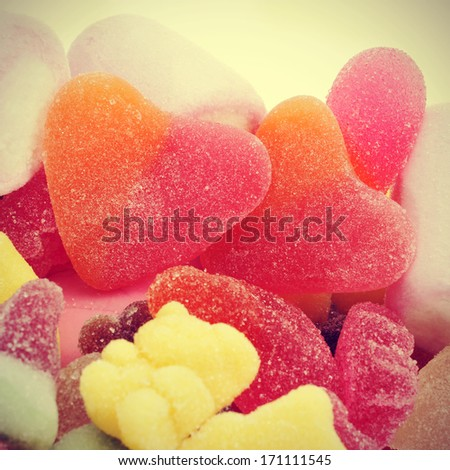 a pair of heart-shaped candies in a pile of different candies, with a retro effect - stock photo