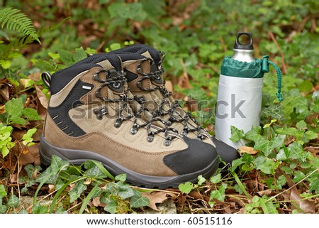A pair of hiking boots and canteen in the field. Shallow depth of field and blurred background - stock photo