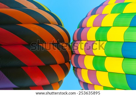 A pair of hot air balloons flying so close they are touching - stock photo