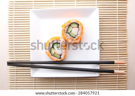 A pair of Japanese sushi roll with chopsticks - stock photo