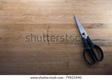 A pair of kitchen shears sits on a worn butcher block counter top - stock photo
