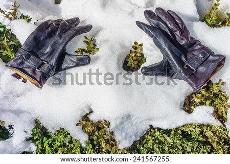 A pair of leather gloves on snow ice - stock photo