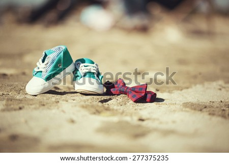 a pair of little baby shoes with a bow tie - stock photo