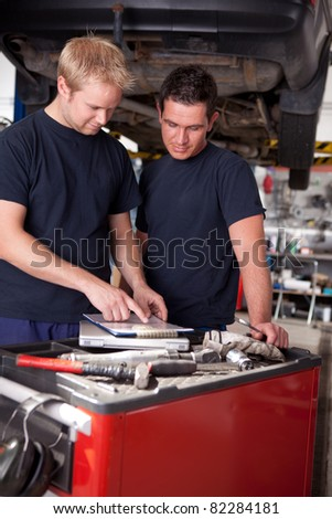 A pair of mechanics working on a car looking a service order - stock photo