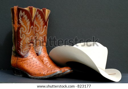 A pair of men's cowboy boots and a dress cowboy hat are ready to be worn - stock photo