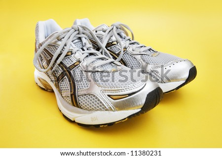 A Pair of men's running shoes on yellow.