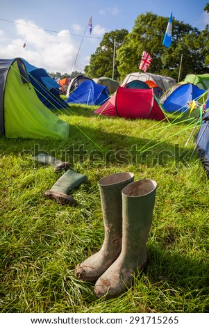 A pair of muddy wellington boots at a British music festival campsite. Shallow depth of field with selective focus on the boots.