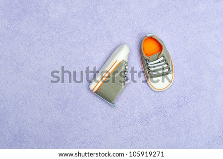 A pair of new baby boy tennis shoes on a purple blanket. Image was shot to leave copy space on the left side for designers. - stock photo