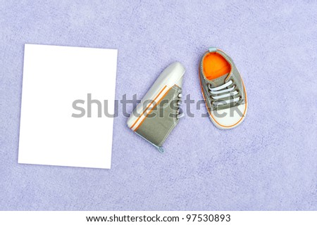 A pair of new baby boy tennis shoes on a purple blanket with blank white card for placement of copy