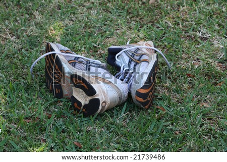 A pair of old running shoes outside on the grass. - stock photo