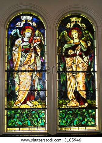 A pair of old stained glass windows circa 1899 showing two angels, labeled as Love and Peace.