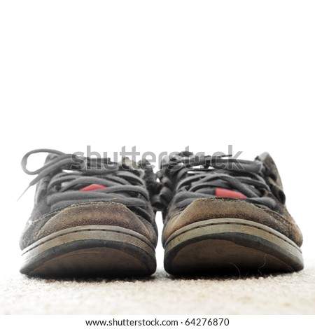 A pair of old worn out skateboarding shoes on a white background. - stock photo