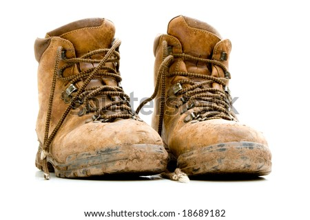 A pair of old worn walking boots isolated on a white background - stock photo