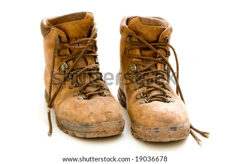 A pair of old worn walking boots isolated on a white background