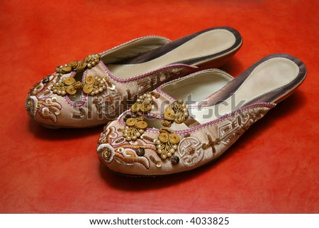 A pair of oriental ladies shoes with exquisite needlework. - stock photo
