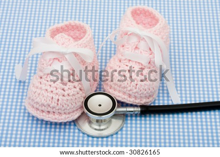 A pair of pink baby booties and a stethoscope on a blue background, Healthcare Costs
