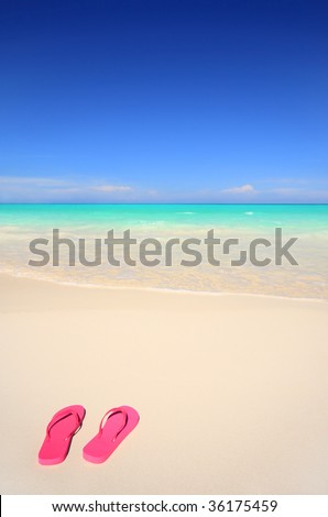 A pair of pink flip-flop sandals on a white sand tropical beach. Beach vacation concept. - stock photo