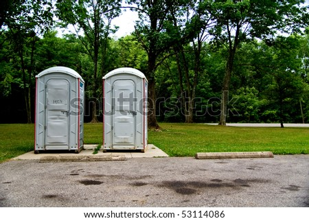 A pair of port a potties in a local area public park. - stock photo