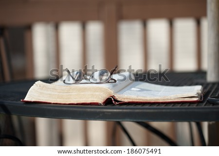 A pair of reading glasses rests on top of an open Bible on a wrought-iron patio table on a wooden deck as the evening shadows settle in. - stock photo