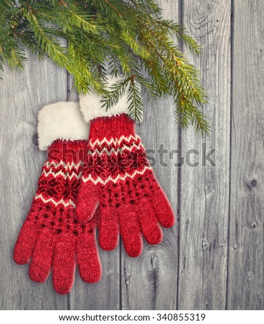 A pair of red gloves hanging on wooden background. - stock photo